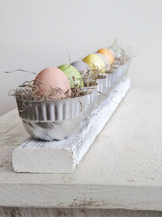 a wooden board, metal cups with straw and pastel-colored eggs