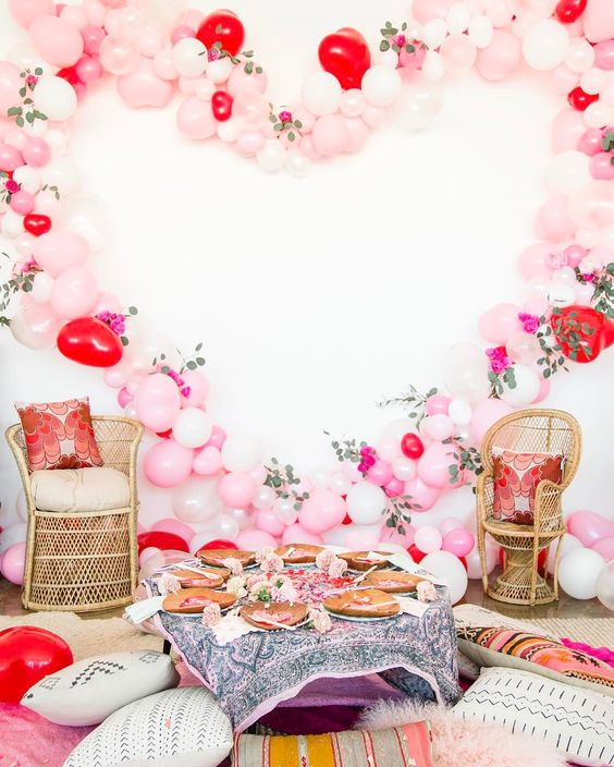 oversized blush and red balloon heart as a backdrop