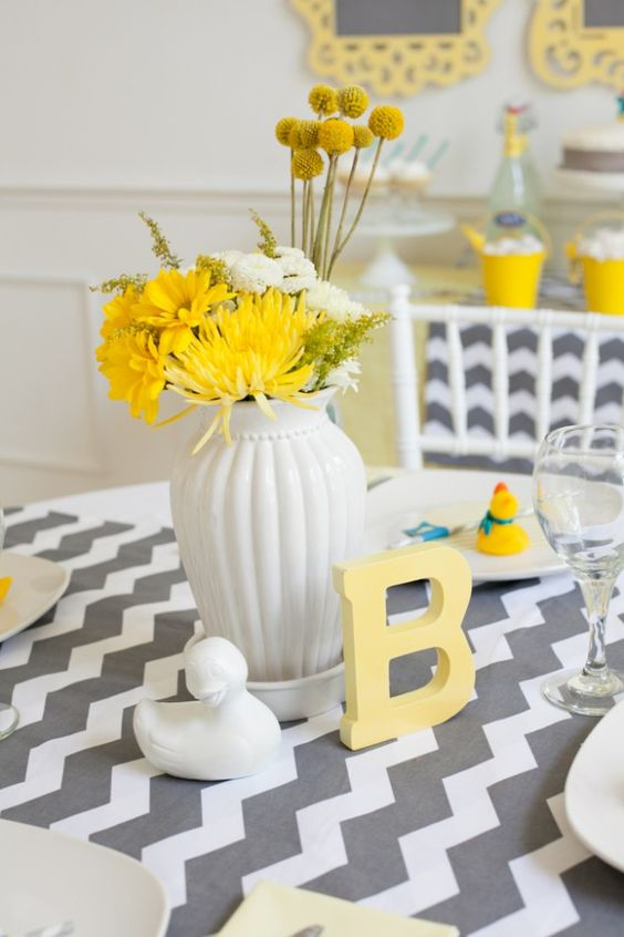 a white vase with white and yellow flowers looks really neutral