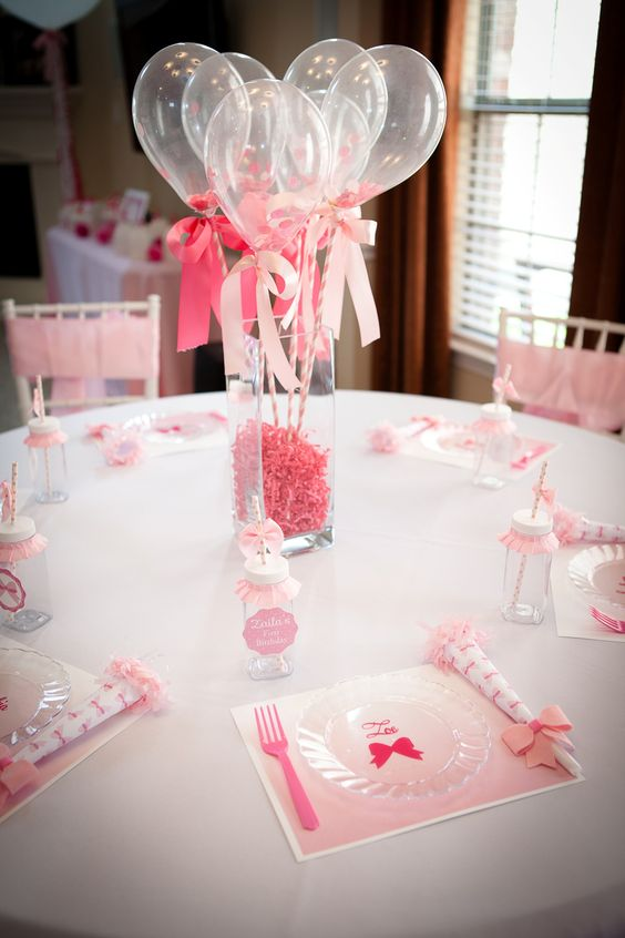 sheer balloons with ribbon bows on sticks, a vase with pink paper