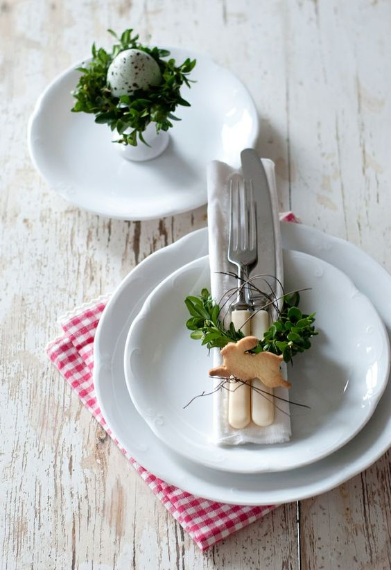 white plates, tableware with greenery and a bunny-shaped cookie