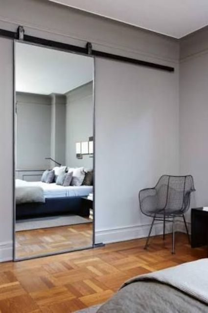 a glass barn door expands the space and works as a mirror too