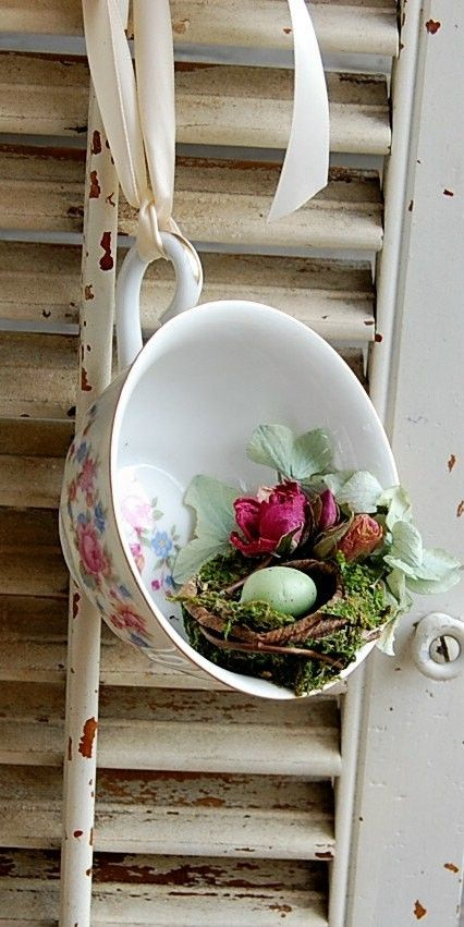 a vintage teacup with dried flowers and a small nest with a green egg