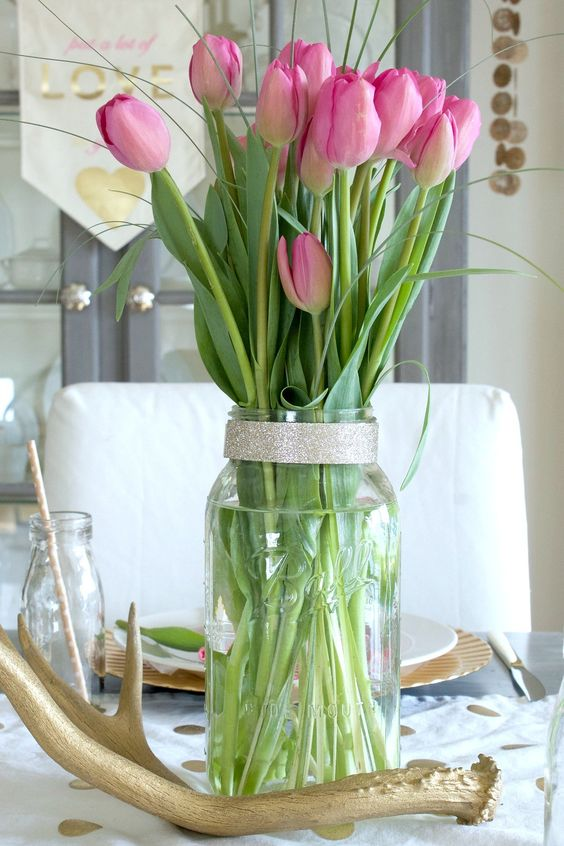 modern elegant centerpiece of a jar with tulips and grasss