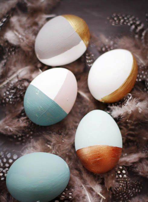 partly painted Easter eggs in pastel and metallic shades
