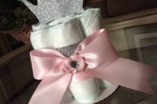 20 a diaper centerpiece with a glitter crown and a pink bow