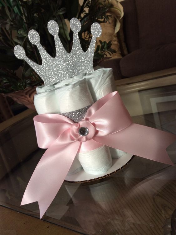 a diaper centerpiece with a glitter crown and a pink bow