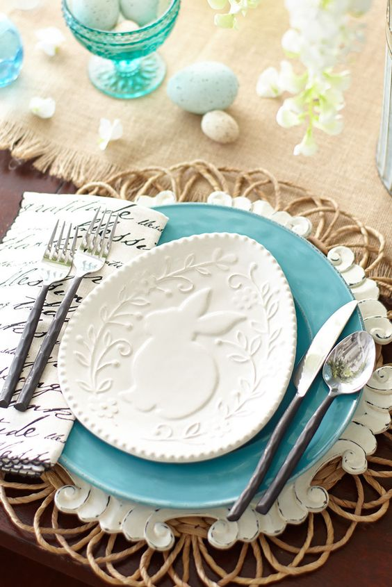 a wicker platter, a blue plate and a bunny plate on top