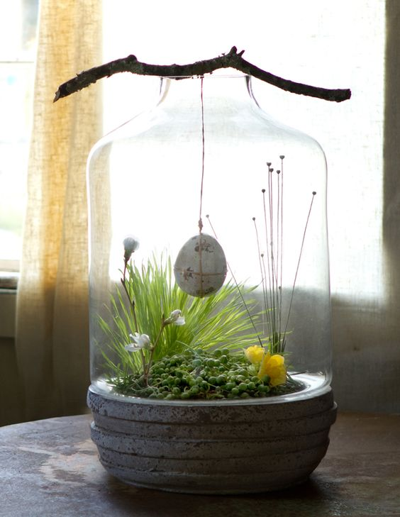 spring terrarium with a concrete base, greenery, snowdrops and an egg hanging