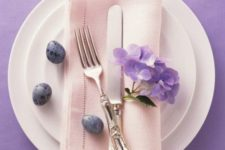 23 white plates, a blush napkin, lavender speckled eggs and purple blooms