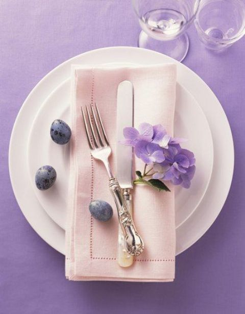 white plates, a blush napkin, lavender speckled eggs and purple blooms
