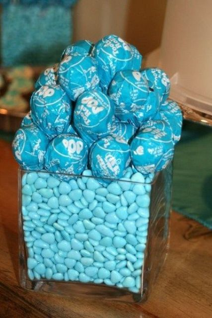 a blue candy centerpiece with blue pops in paper