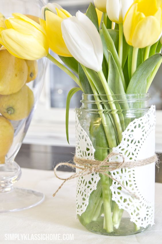 a mason jar covered with a doily and twine, fresh spring blooms