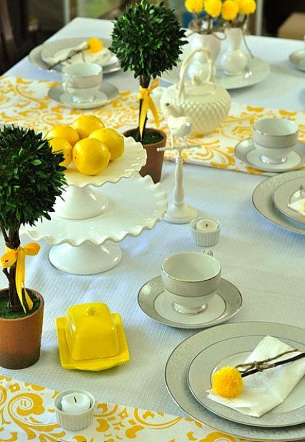 a mint tablecloth with yellow patterned textiles and yellow dishes