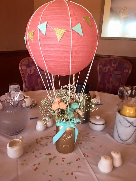 a coral hot air balloon centerpiece with a gilded mason jar and flowers