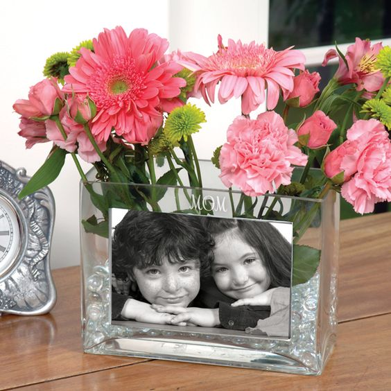 a glass vase with a kids' photo and pink flowers