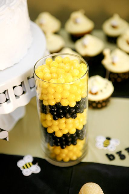 a glass vase with yellow and black candies for a bee-themed party