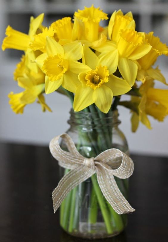 a mason jar with a burlap bow and yellow daffodils
