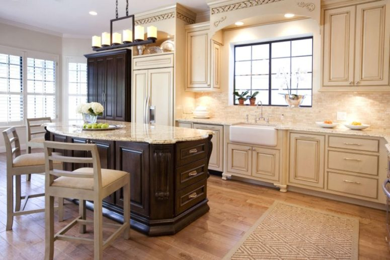 a dark cabinet and kitchen island help the cream colored kitchen stand out