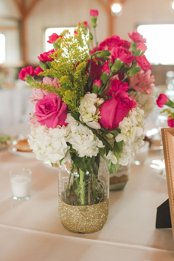 a half glittered mason jar with fuchsia and white flowers