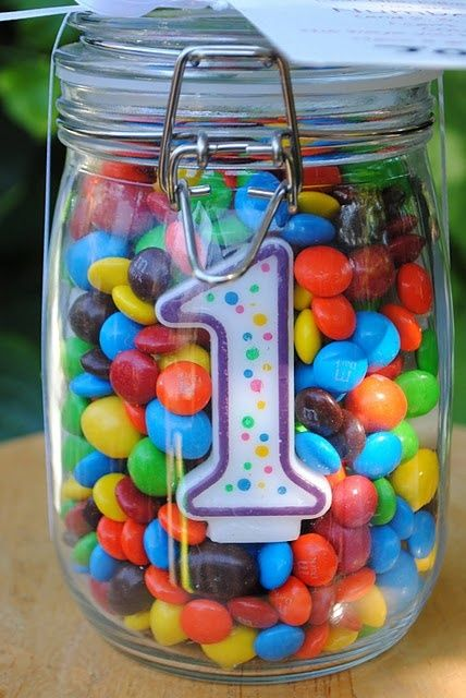 a jar filled with M&Ms with a candle inside