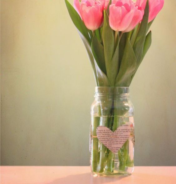a mason jar with a paper heart and pink tulips