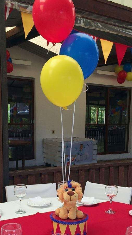 a stuffed toy on a drum and bold balloons for a fun party