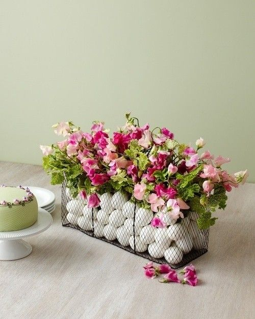 a wire basket with white eggs and colorful florals