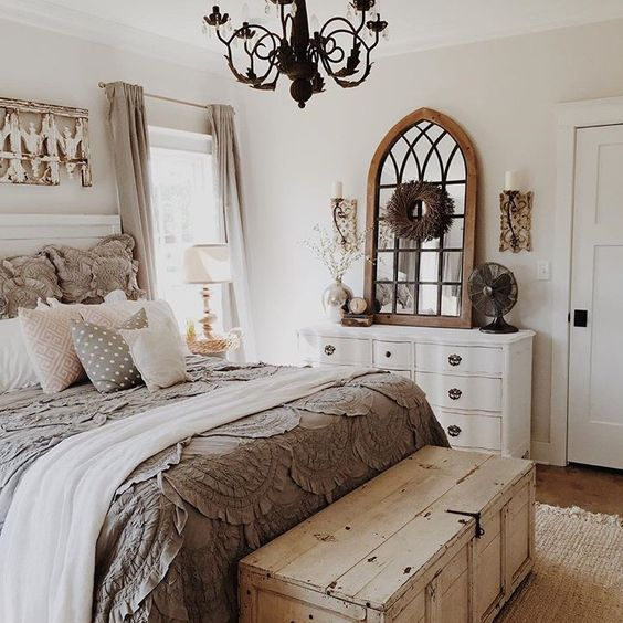 neutral bedroom decor with a rustic chest and a refined white dresser, shabby chic details and exquisite lights