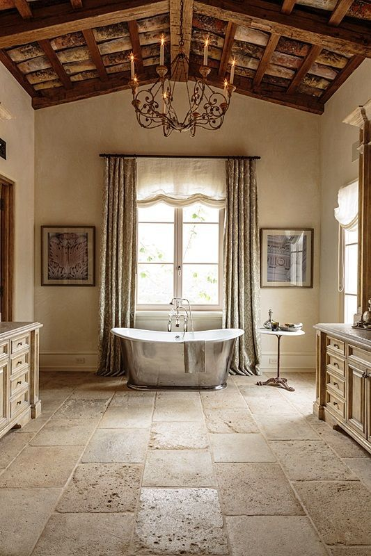 soft buttermilk bathroom with textural stone floors and a wooden ceiling