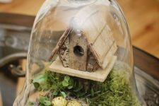 05 a cloche with a bird house, greenery and a faux nest with eggs