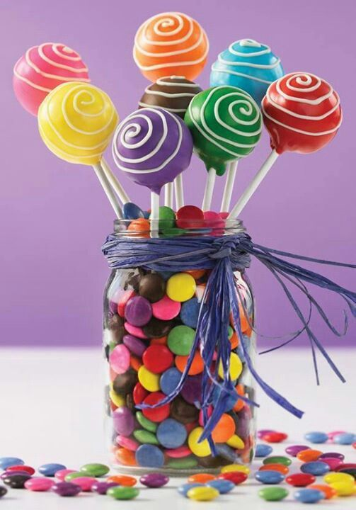 a jar with colorful M&Ms and cake pops to top