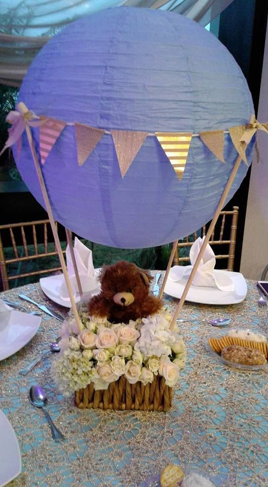 a purple lantern with a bakset with a teddy bear inside