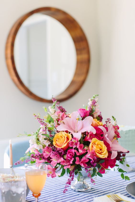 a very colorful floral arrangement in orange, pink and fuchsia