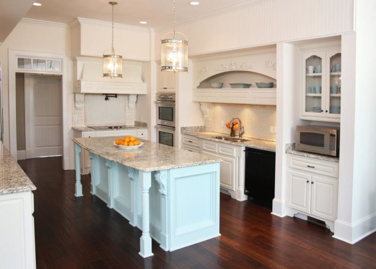 a white kitchen with a mint kitchen island and grey marble countertops