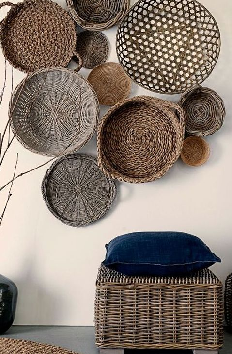 a wicker pouf echoes with wall baskets and creates a stylish entryway