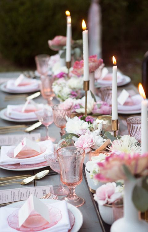 pink glasses and plates echo with pink blooms on the table
