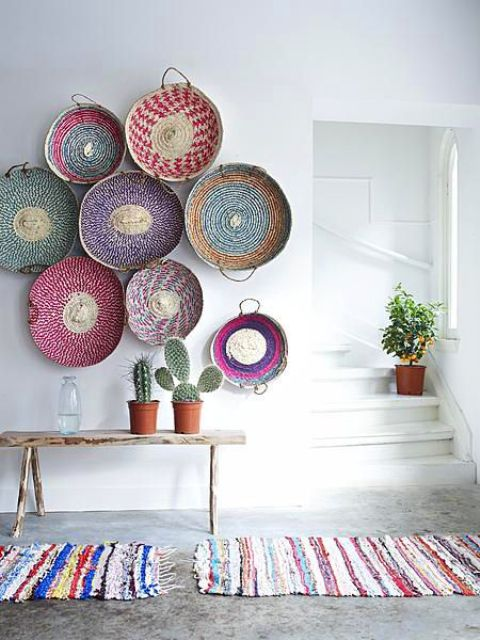 a boho ethnic entryway is decorated with colorful wall baskets and rugs