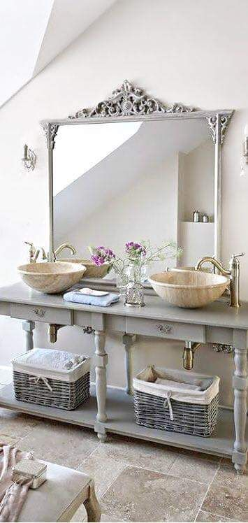 a grey vanity with a refined mirror frame and baskets for storage