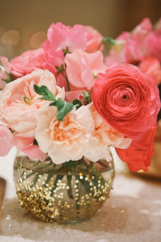 a sheer vase with gold sequins and bold pink flowers