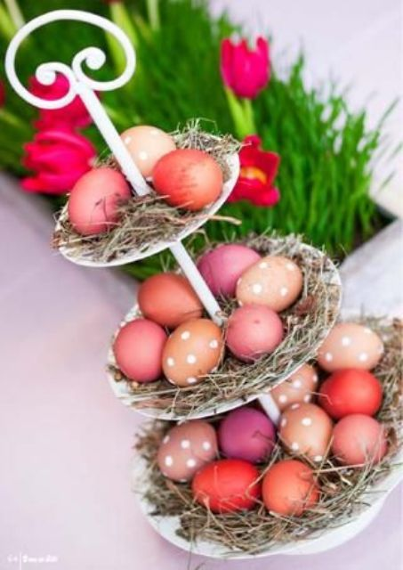 a cupcake stand covered with straw and with colorful eggs