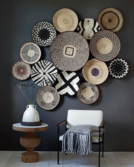 a dark space is enlivened with white furniture and graphic painted baskets on the wall