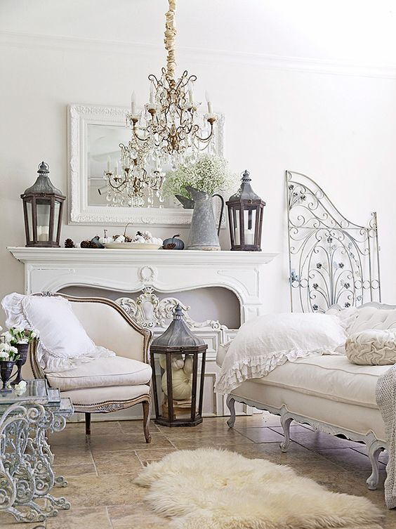 a faux fur rug, metal lanterns, a crystal chandelier and a foraged decoration add interest to the room