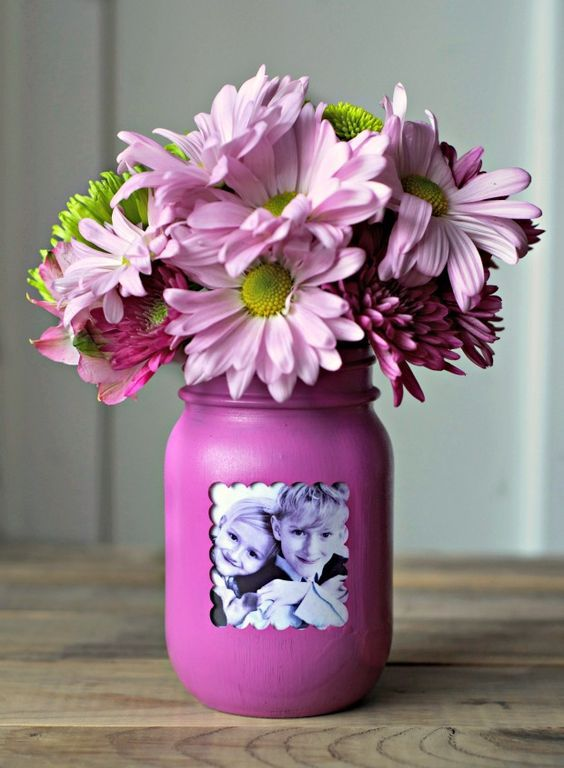 a purple mason jar with a kid's photo and pink flowers