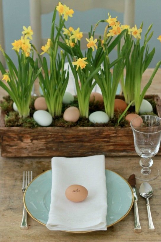 a reclaimed wooden box with moss, pastel eggs and yellow daffodils