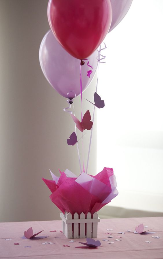 a fence with colorful paper and balloons with butterflies for a girl's party