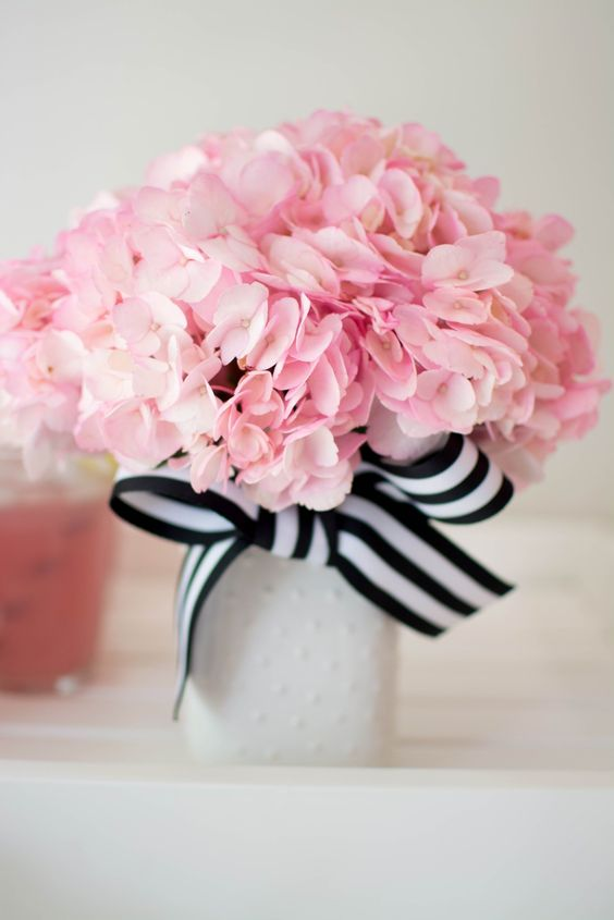 a neutral vase with a striped black and white bow and pink flowers