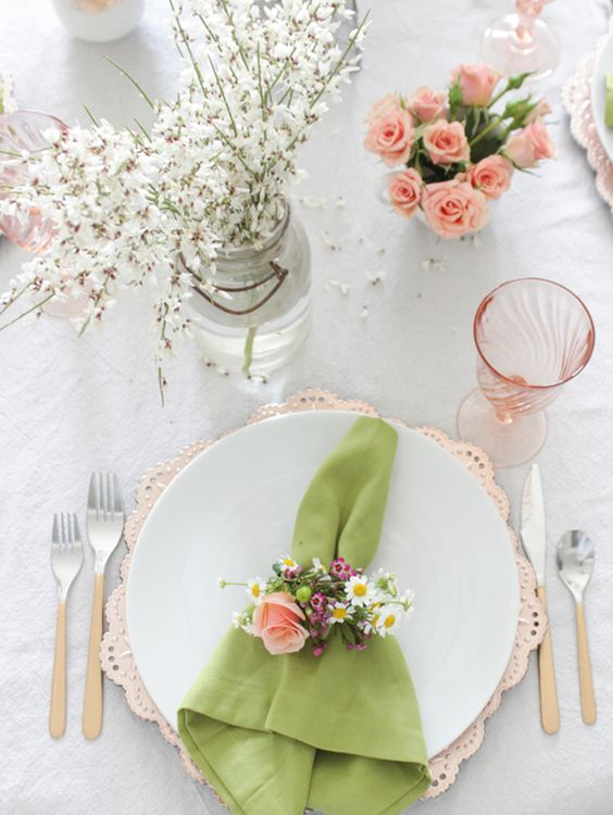 a rather neutral table is enlivened with a green napkin and some pink roses