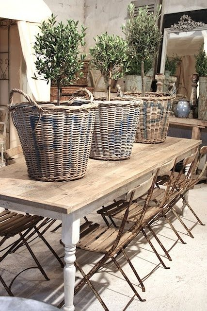 a rustic table, shabby forged chairs and baskets as planters