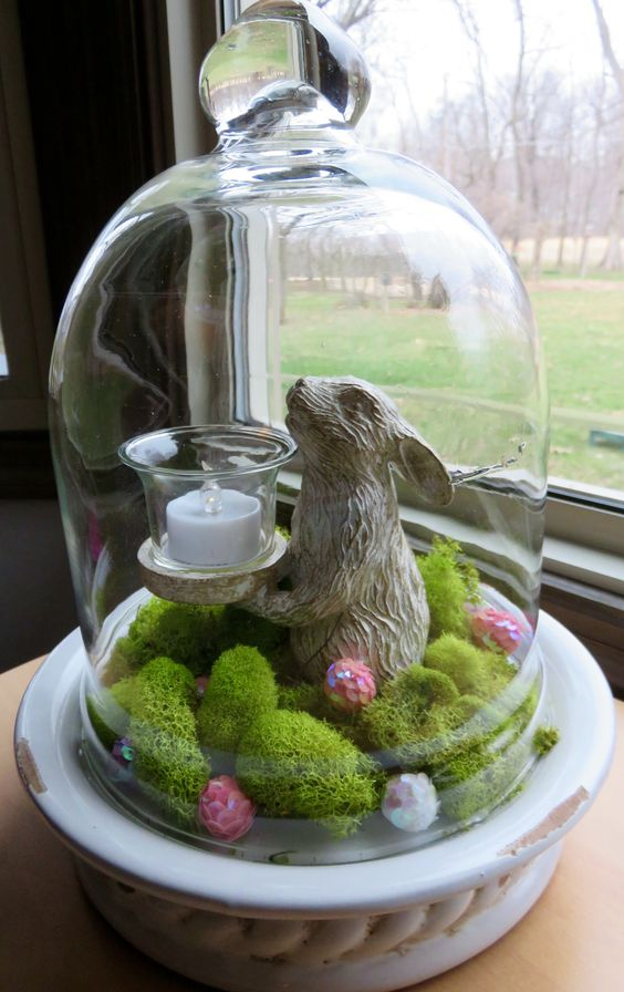 a cloche with moss and sequin eggs, a bunny candle holder